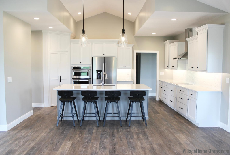White kitchen with large gray island, glass pendants, and light wood floors.
