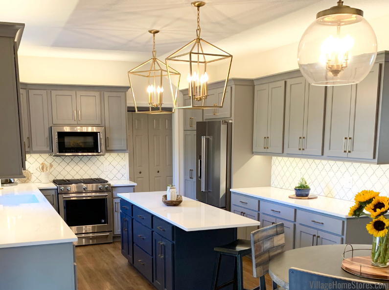 gray and blue cabinet kitchen with gold lighting above island and table.