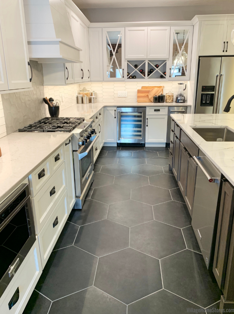 """Village Home Stores Koch Cabinetry kitchen in """"Bristol"""" door and white paint with Rift Oak island in the """"Silverwood"""" stain. Matte black large hex tiles on floor also featured.."""