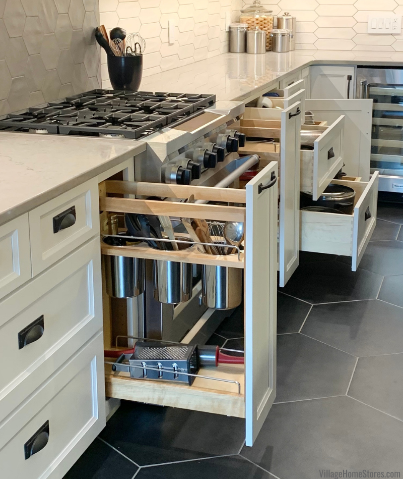 Pull out utensil and spice storage in a white painted kitchen with hexagon floor tile