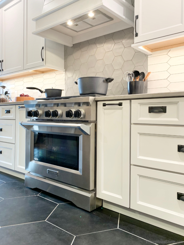 Wood hood with range hood insert above a KitchenAid Stainless Steel commercial style range.