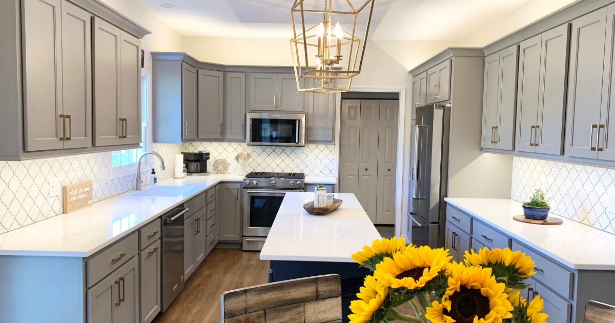 Kitchen with gray cabinets, dark blue island, and light quartz countertops. Fresh sunflowers in the foreground.