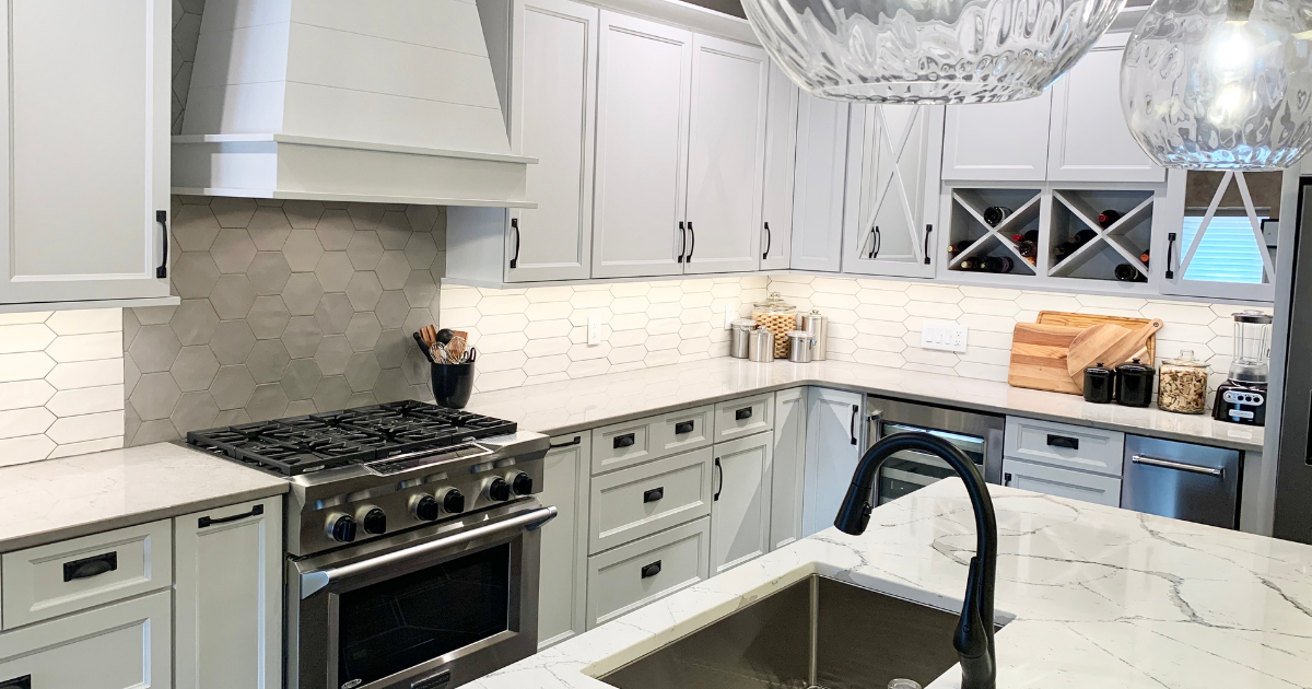White cabinet kitchen by Village Home Stores with Cambria Quartz counters and crayon and hex shaped wall tile