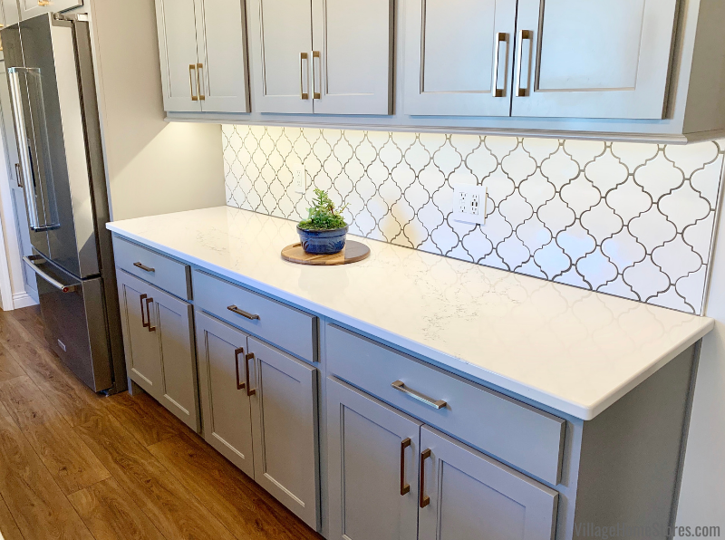 Arabesque shaped tile as kitchen backsplash with gray painted cabinets and light quartz counters.