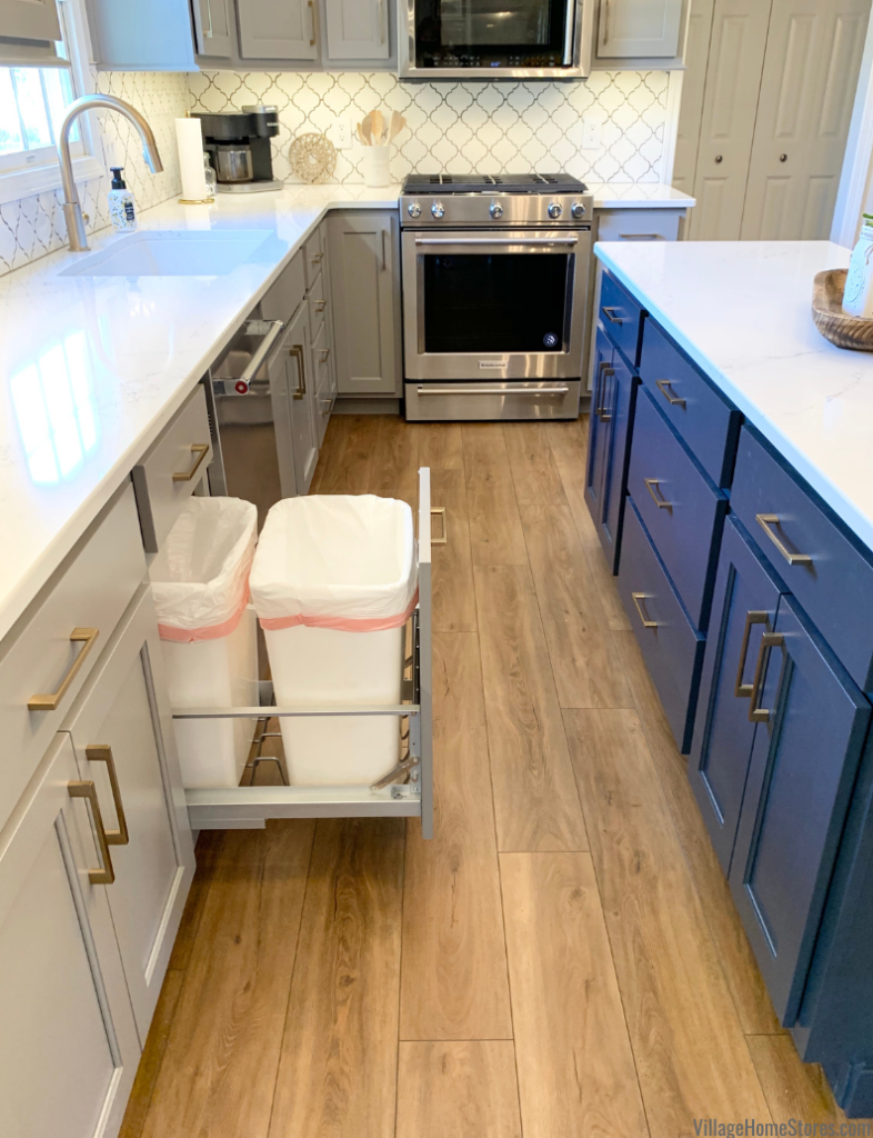 gray and blue cabinet kitchen with light luxury vinyl plank flooring.