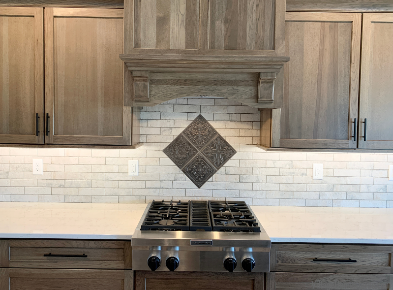 Elongated subway tile kitchen backsplash with tin look tile accent area above gas cooktop in diamond pattern.