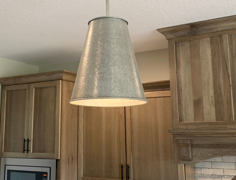 Ari metal pendant lights by Capital Lighting hang above a kitchen island from Village Home Stores