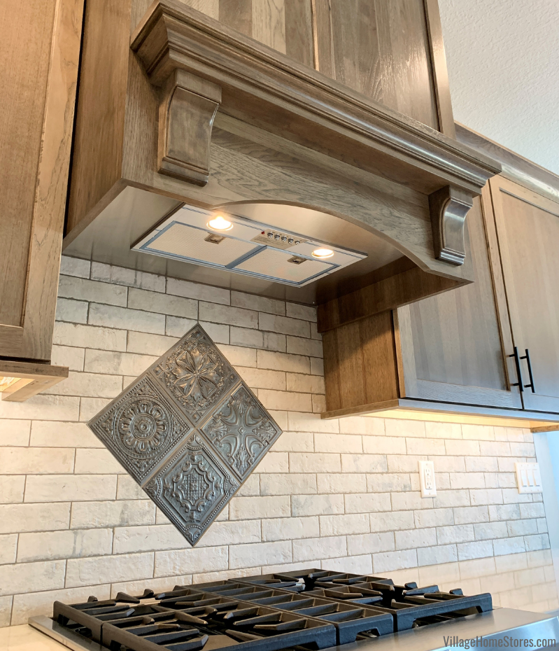 Broan 500 CFM range hood insert in a wood range hood cabinet with mantle shelf. Tin look accent tile below for area above gas cooktop.