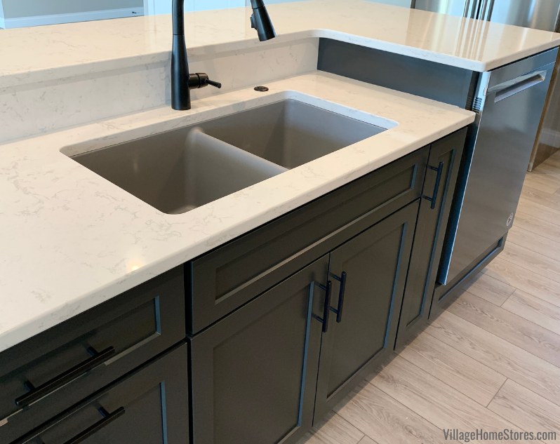 Cambria Torquay quartz counters on dual level island with gray undermount sink and matte black faucet with disposal button.