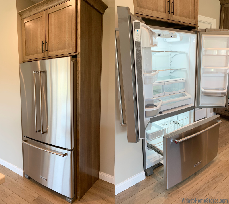KitchenAid french door counter depth refrigerator with interior water dispense. Refrigerator wood end panel and cabinet above build in the design.