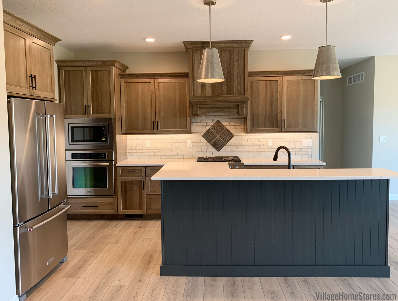 Hickory kitchen with Morel stain and painted Graphite island, medium wood luxury vinyl plank flooring, and metal pendant lighting