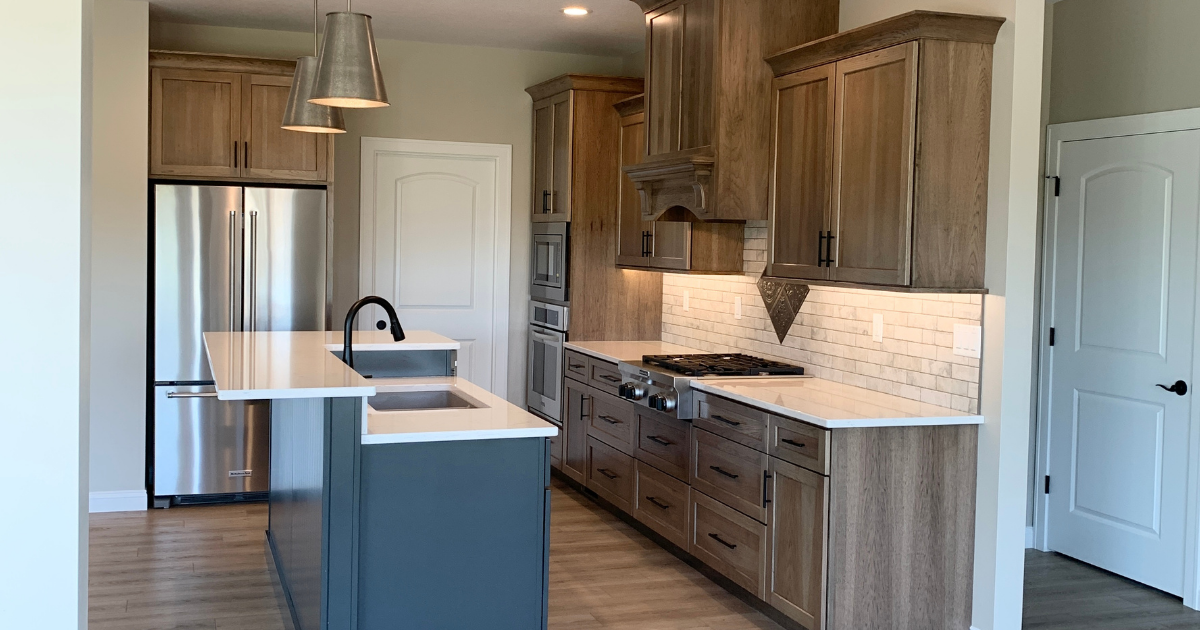 A Dura Supreme Hickory kitchen in the Hudson door with Morel stain and painted Graphite island. Two level island with metal pendants hanging above.