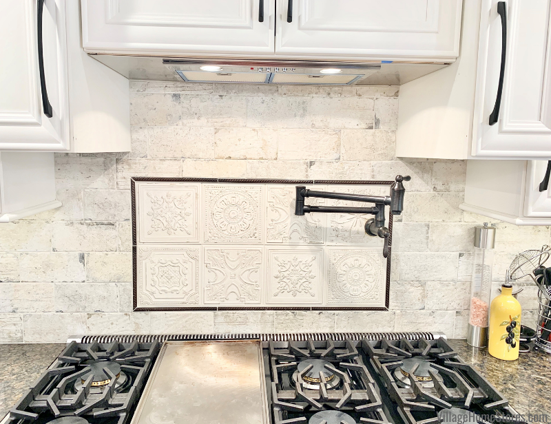 Kitchen with accent tile and potfiller faucet above cooktop