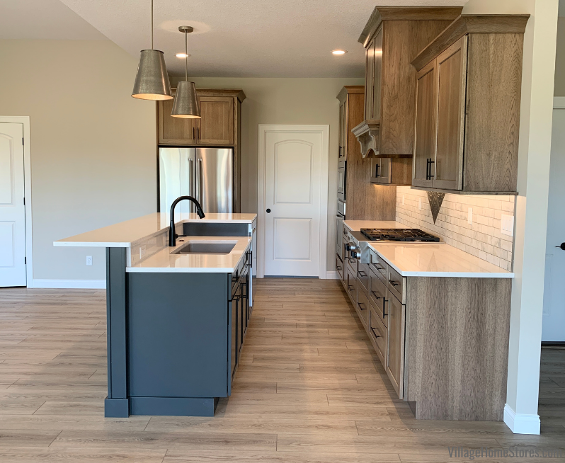 Hickory kitchen with warm gray stain and Graphite painted dual-level island. Medium oak luxury vinyl plank flooring and metal pendants also featured.