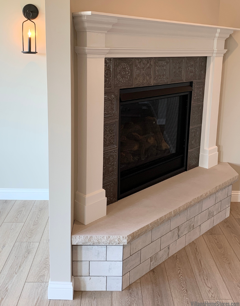 Tin look tile as fireplace surround in a new home in Geneseo, IL with tile and flooring by Village Home Stores