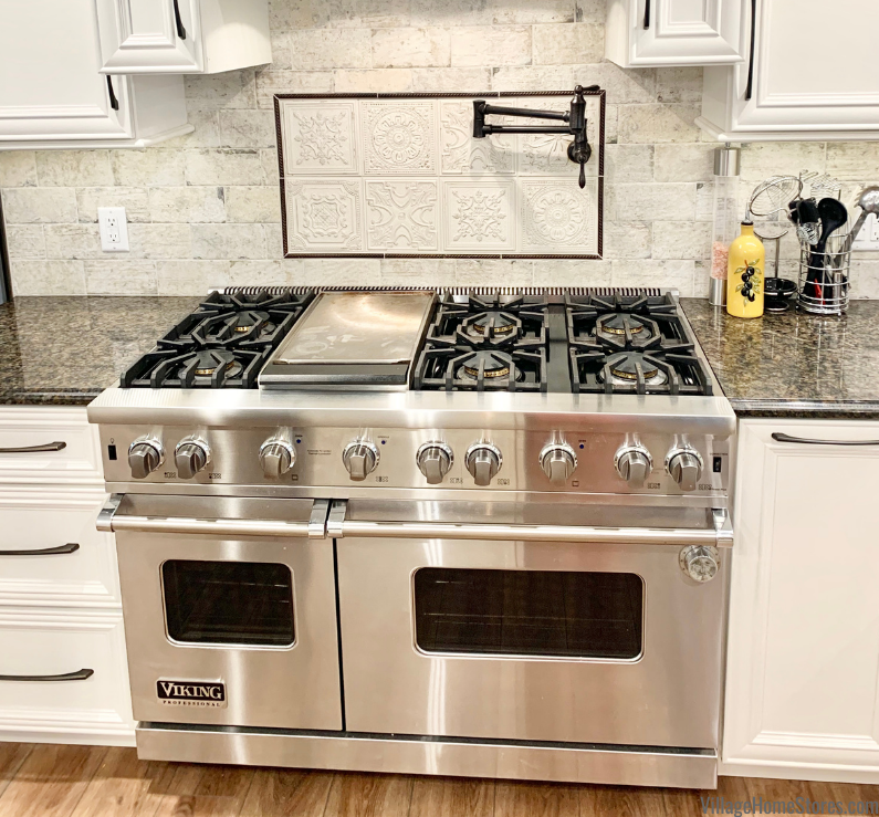 Viking range with griddle and wall faucet pot filler in a Geneseo, IL kitchen by Village Home Stores