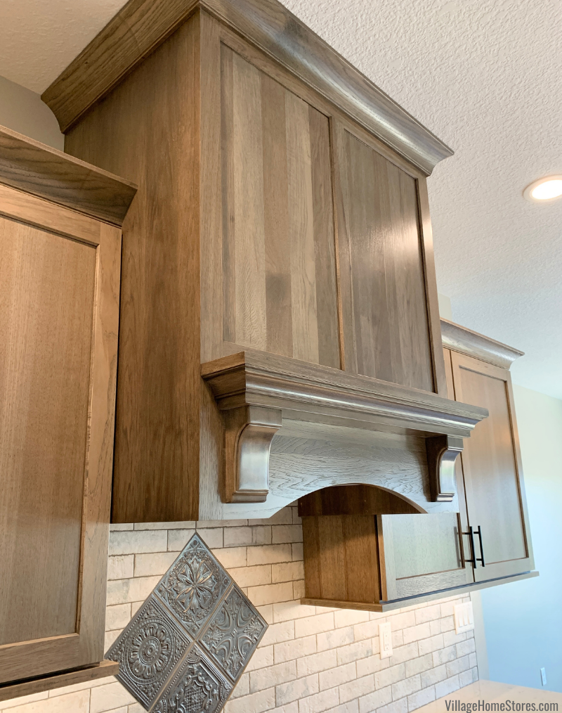 Wood range hood cabinet with mantle in a Hickory kitchen in the warm Morel stain