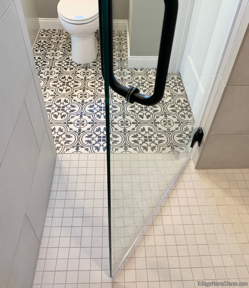 A view out of the custom tiled shower showing Daltile's Petal Black Memoir 12 x 12 tiles in a primary bathroom.