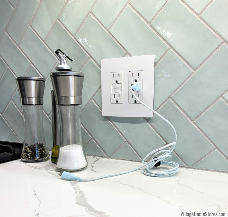 Kitchen outlet with USB inserts on Village Mint green wall tiles in a sideways herringbone tile pattern. Design and materials by Village Home Stores.