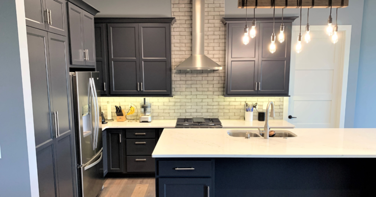 kitchen with hanging Edison bulb light and dark blue cabinets