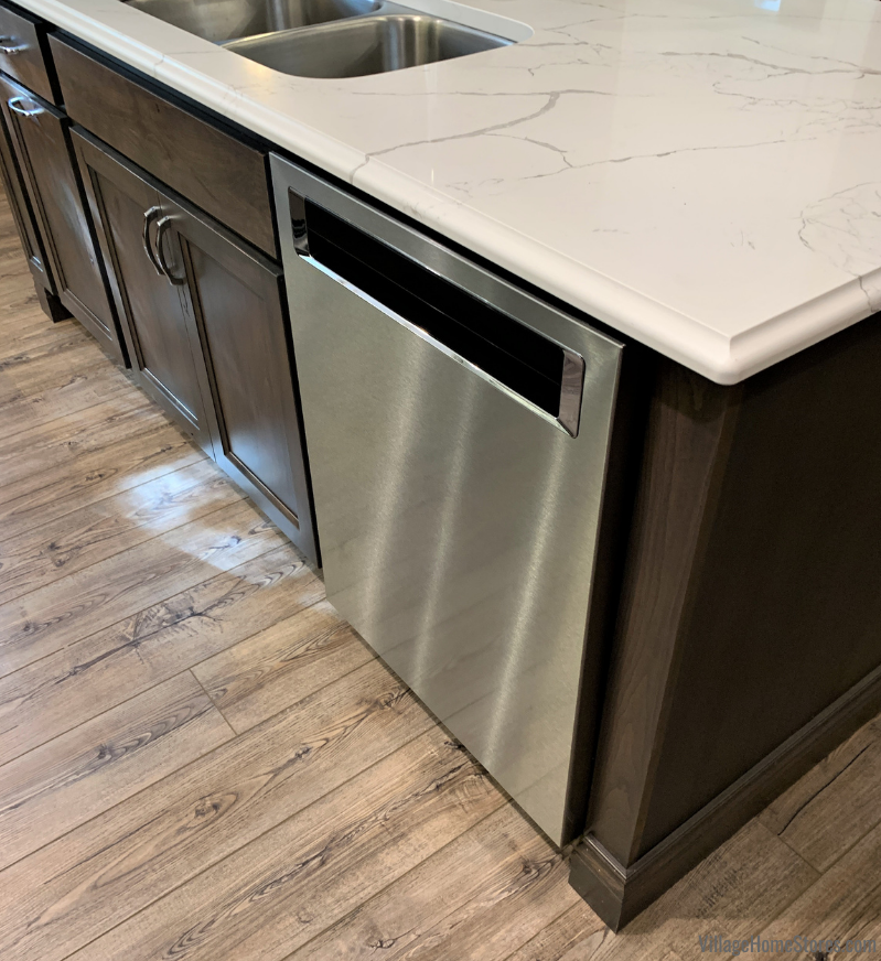 Kitchen island in Koch Rustic Beech Stone with Stainless Steel KitchenAid dishwasher. Design and materials by Village Home Stores.