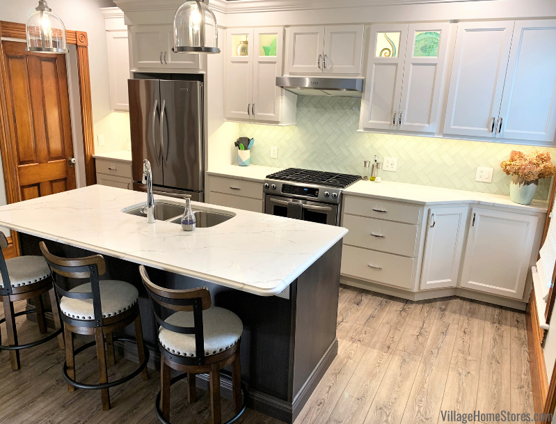 Old home kitchen remodel with Koch cabinets, quartz counters, sea glass green wall tiles, and luxury vinyl plank floors. Design and materials by Village Home Stores.