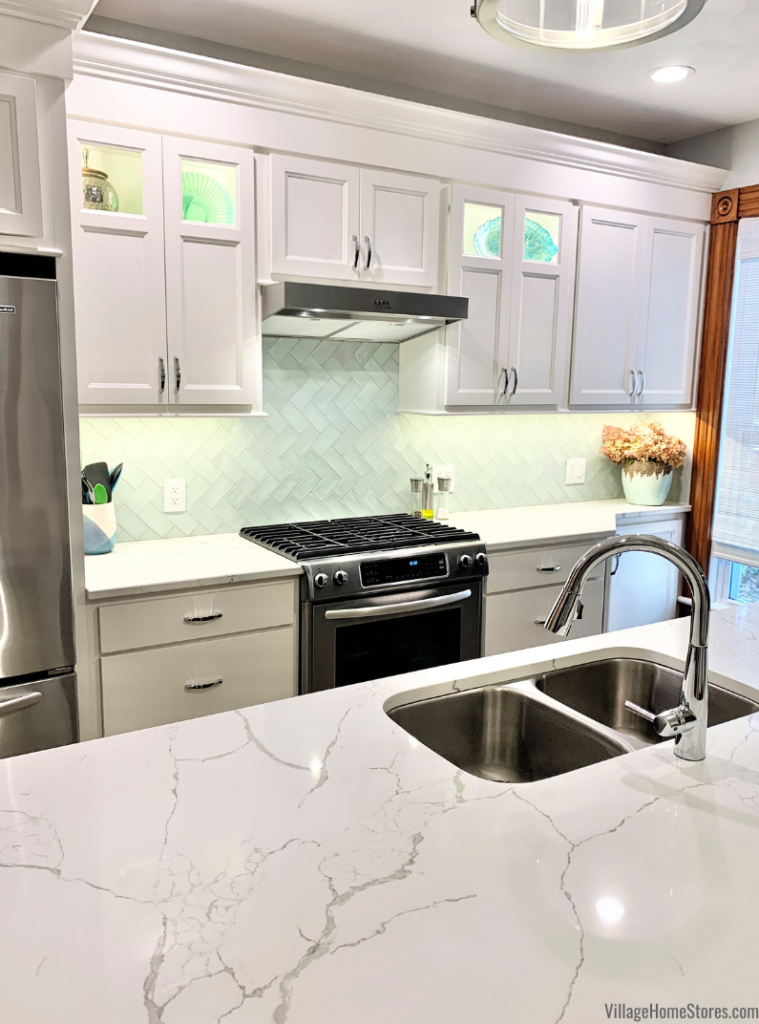Kitchen with mint green wall tiles and white MSI Calacatta Laza quartz counters. Design and materials by Village Home Stores.