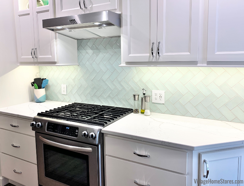 Kitchen with Village Mint green wall tiles in a sideways herringbone tile pattern. Design and materials by Village Home Stores.