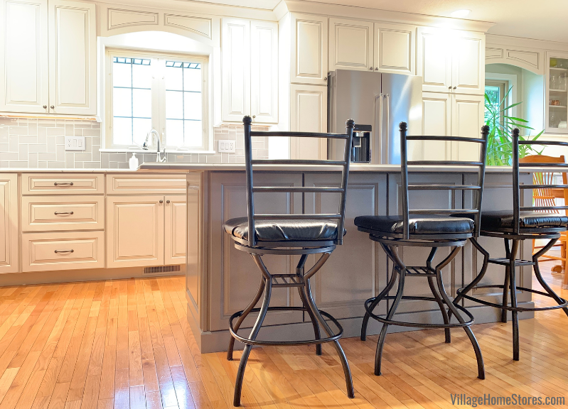 Kitchen island with counter height seating overhang. Koch cabinetry in the Easton door and a combination of Ivory with Smoke highlight and Fog painted finishes.