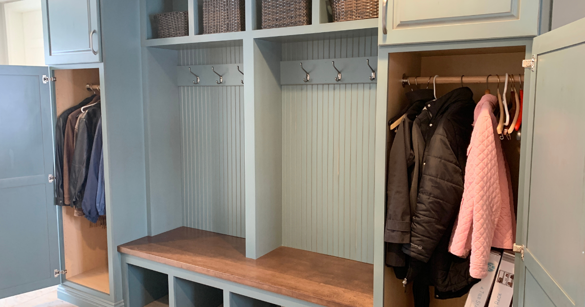 Painted teal Capri Drift finish by Koch Cabinetry on mudroom bench with wood seat and coat storage