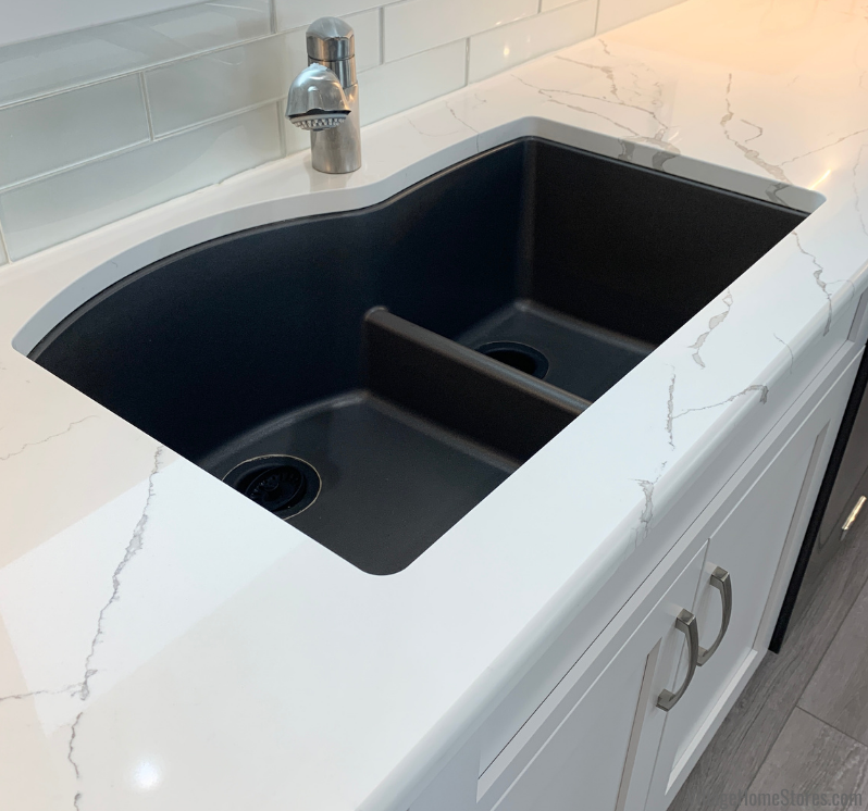 Black granite undermount kitchen sink with low divider installed in white quartz counters.