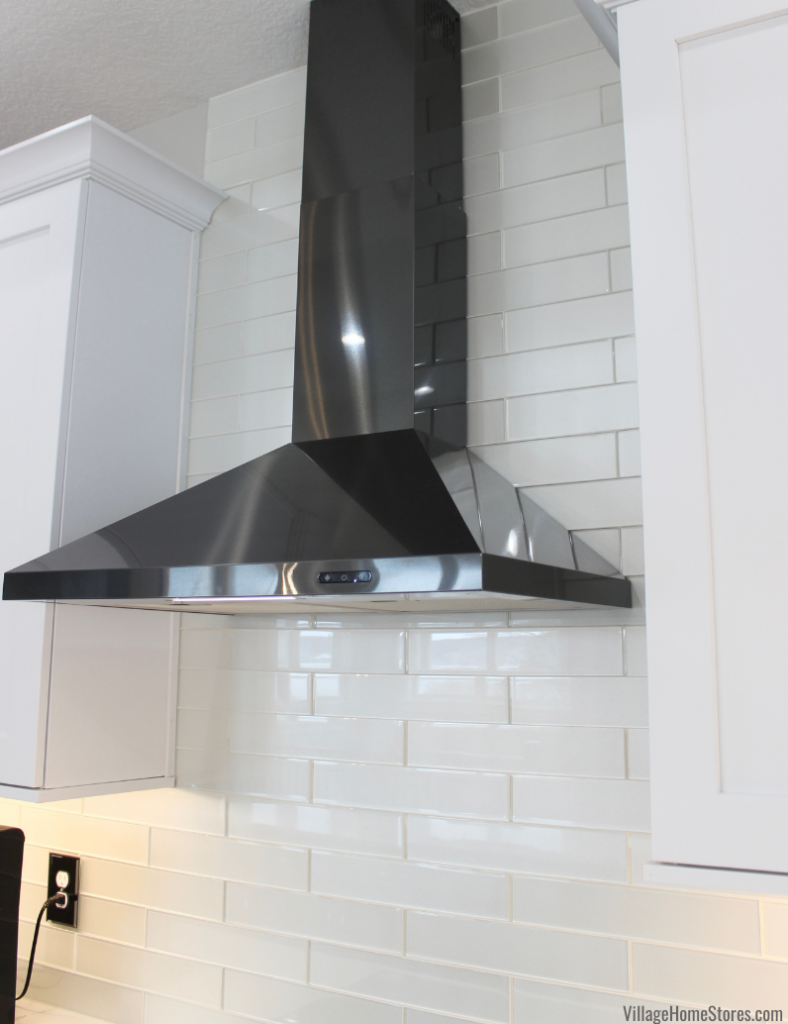 Black Stainless Steel canopy range hood installed over elongated glass wall tiles.