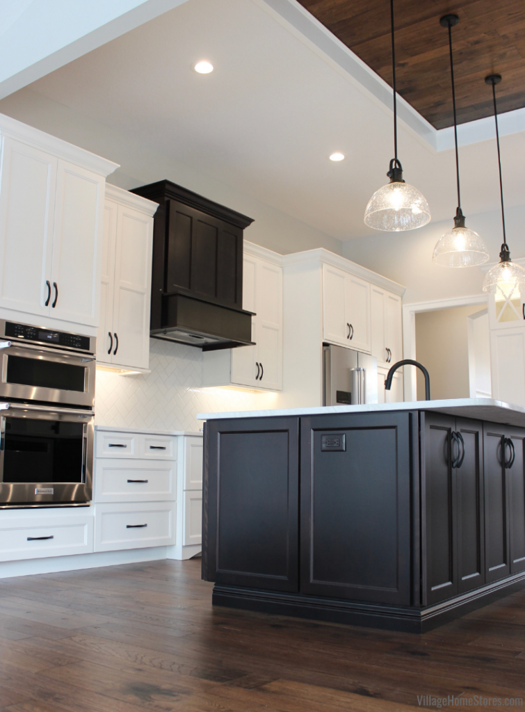 Great room kitchen with Ivory and Java cabinets and seeded glass matte black pendants above kitchen island.