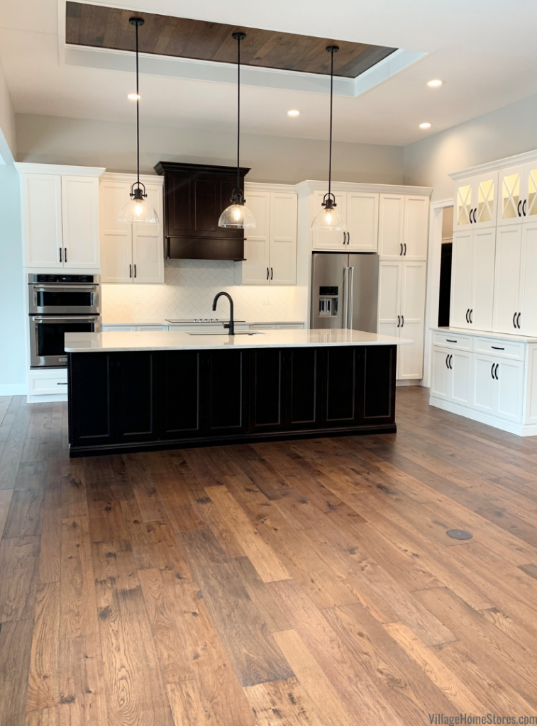 Hallmark wood flooring on floors and tray ceiling of a great room kitchen. Hallmark flooring by Village Home Stores for Hazelwood Homes of the Quad Cities.