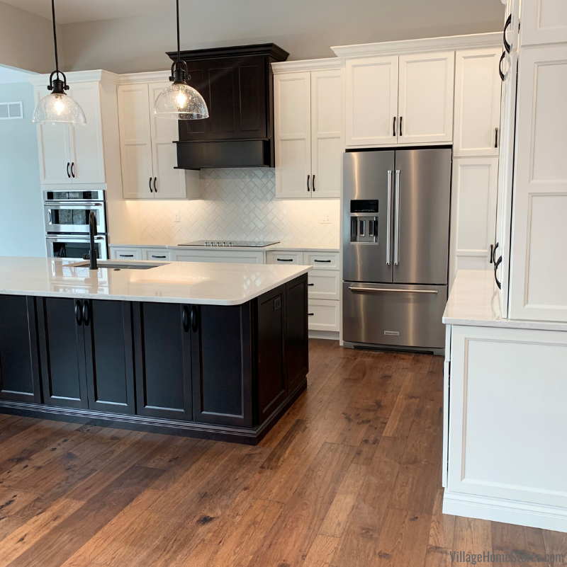Great Room kitchen features Koch Classic Cabinetry in Ivory Paint with a Birch Java island. Stainless Steel KitchenAid appliances, Cambria Quartz Ironsbridge countertops, and seedy glass matte black pendants are also featured.