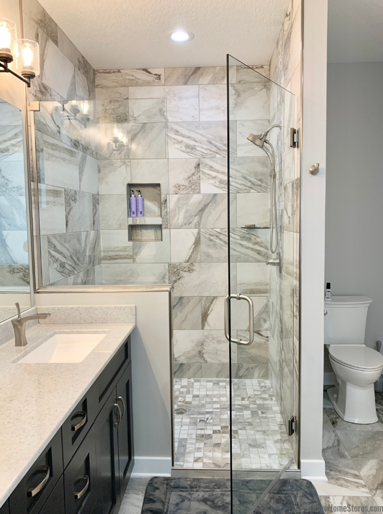 Primary Bathroom with Wynnbrooke Cabinetry in Pewter paint and custom tiled shower with glass panel and door.