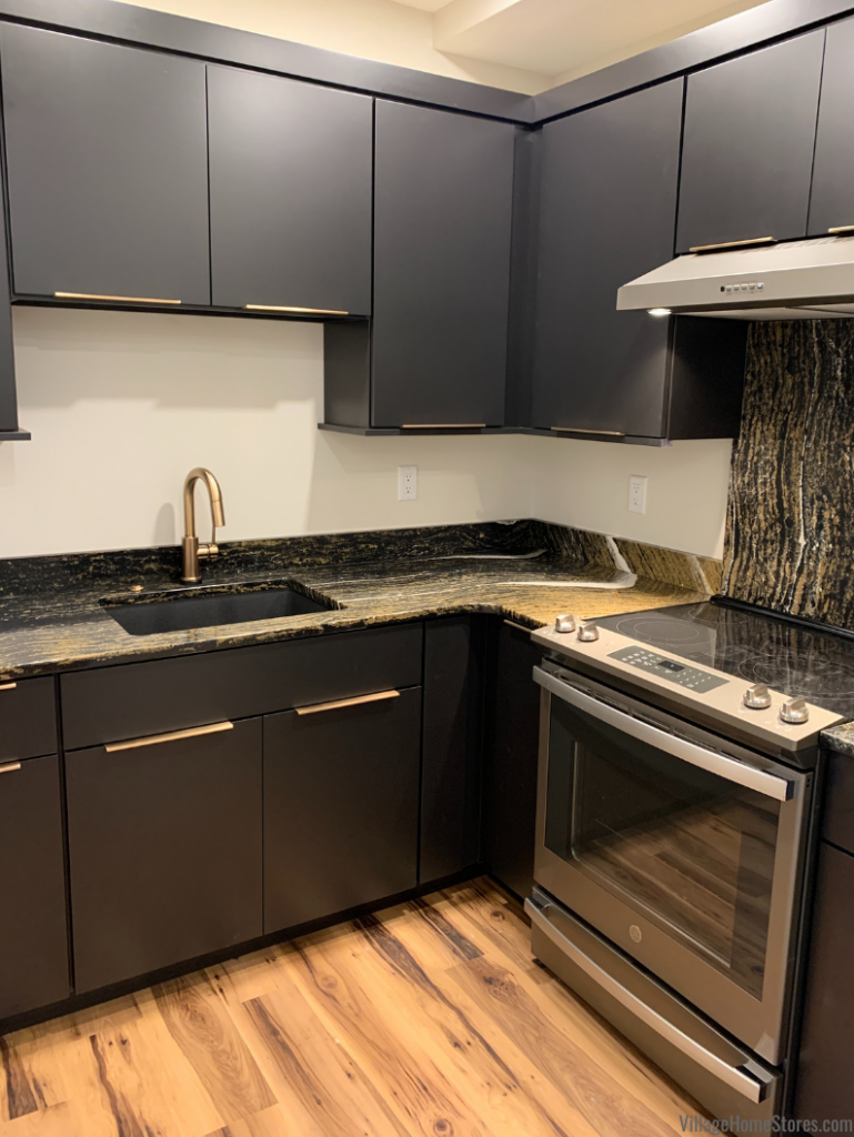 Custom Tricorn Black painted kitchen cabinets in slab doorstyle with sleek squared moldings and Golden Dragon Cambria Quartz tops.