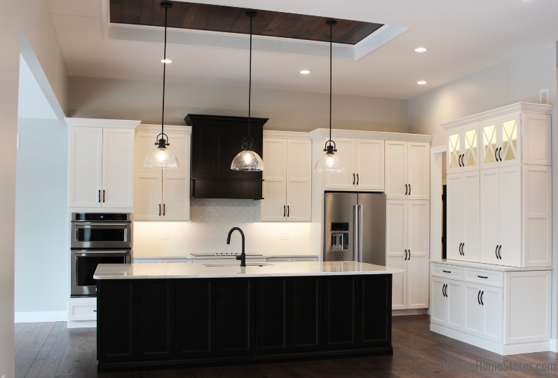 Great room kitchen with Koch Classic Cabinetry in the Bristol door painted Ivory with a Birch Java island. Stainless Steel KitchenAid appliances, Cambria Quartz Ironsbridge countertops, and seedy glass matte black pendants are also featured.