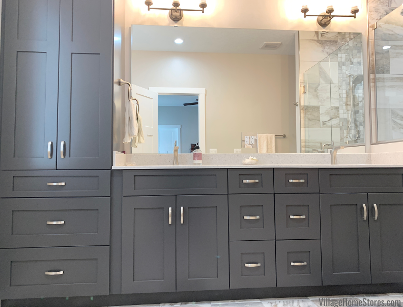 Wynnbrooke Cabinetry in Delani door and painted Pewter finish installed as bathroom cabinetry with double sink layout and linen cabinet.