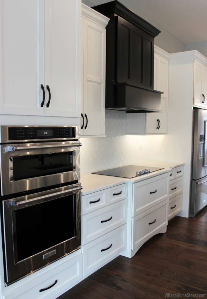 Koch Cabinet kitchen in Ivory Paint with Birch Java wood range hood, KitchenAid appliances, and Cambria Quartz Ironsbridge countertops. Kitchen design and materials by Village Home Stores for Hazelwood Homes of the Quad Cities.