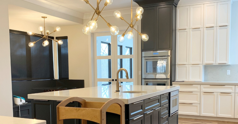 White and gray painted kitchen with modern cabinetry and sputnik style gold island lighting