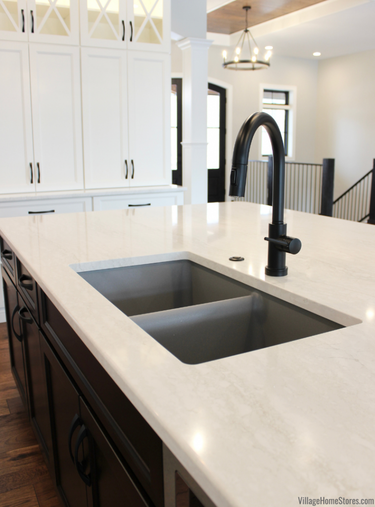 Cambria Quartz Ironsbridge countertops installed with a gray undermount sink and matte black faucet and disposal button. Kitchen design by Village Home Stores for Hazelwood Homes of the Quad Cities.