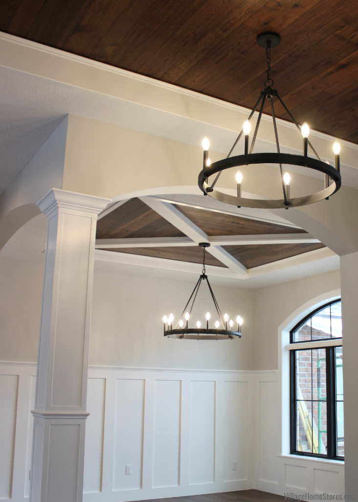 Quorum black circle chandeliers hanging in foyer and dining room of new home with X and wood ceiling detail.