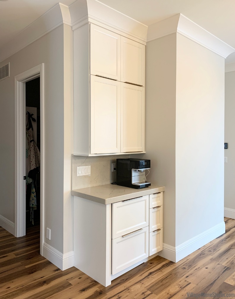 Coffee station zone in kitchen with extra tall painted white wall cabinetry and oversized crown molding.
