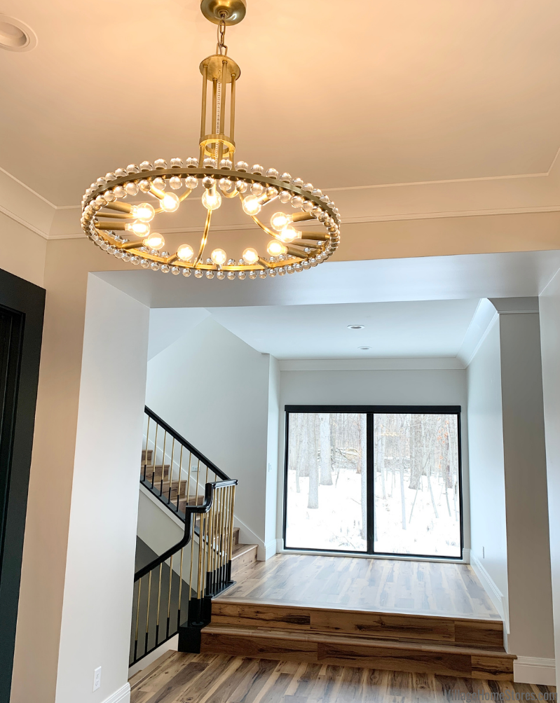 Crystorama Clover Aged Brass chandelier in Aged Brass finish with view to modern stairwell with black framed window.