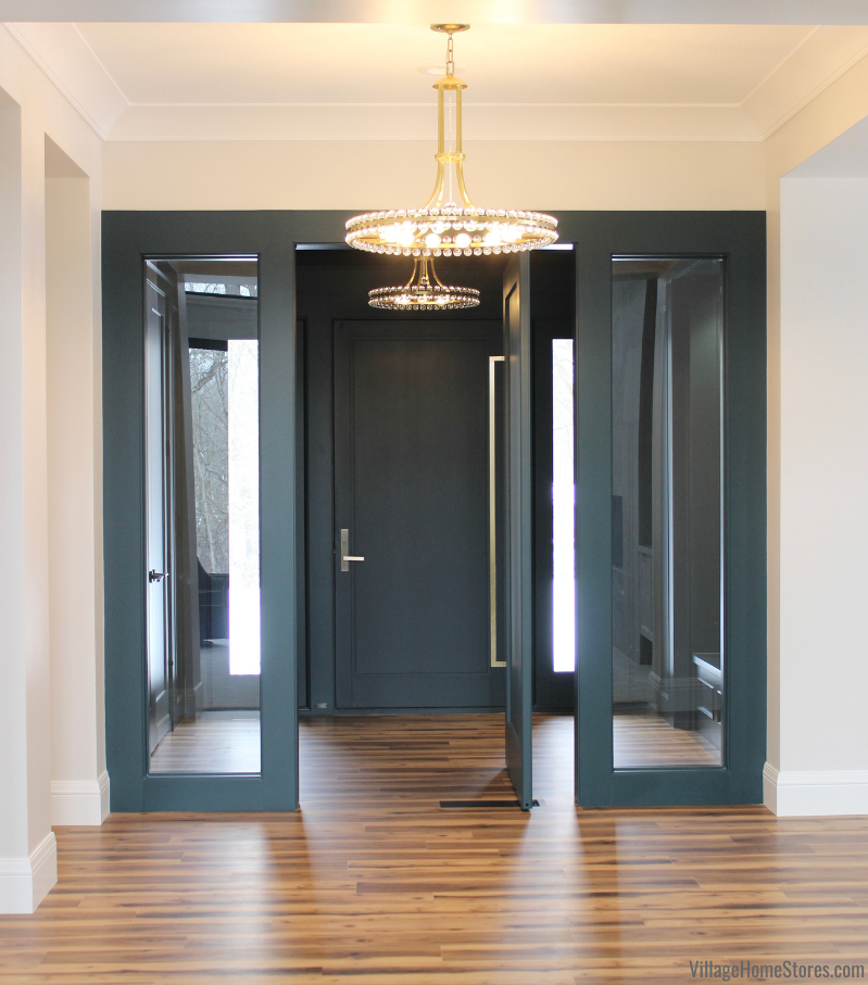 Crystorama Clover Aged Brass chandeliers hanging in entry and airlock of a modern new home built n Bettendorf, Iowa. Painted dark teal wall paneling and bench shown.