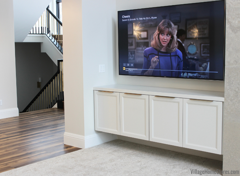 Custom floating white TV cabinet with doors and cheers playing on wall mount flatscreen above