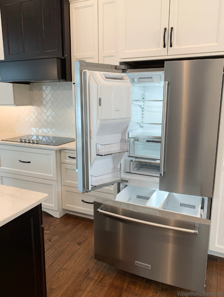 French Door refrigerator with door open installed in a Coal Valley Illinois kitchen from Village Home Stores for Hazelwood Homes.