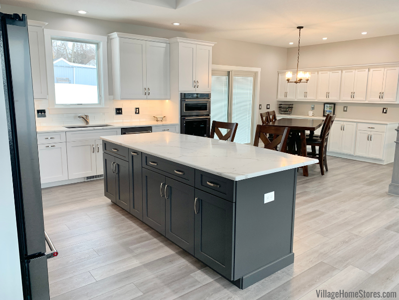 New home kitchen with Pewter painted island. Black Stainless Steel KitchenAid appliances, Q Quartz countertops and our COREtec luxury vinyl plank flooring also featured.