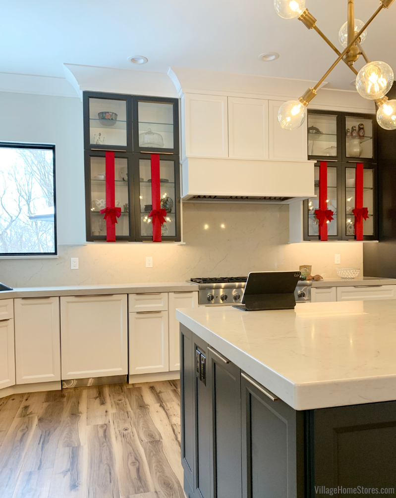 white and gray kitchen with red ribbon decorating the wall cabinet doors for Christmas